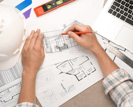 Man hands drawing house plans with construction helmet and laptop on the side